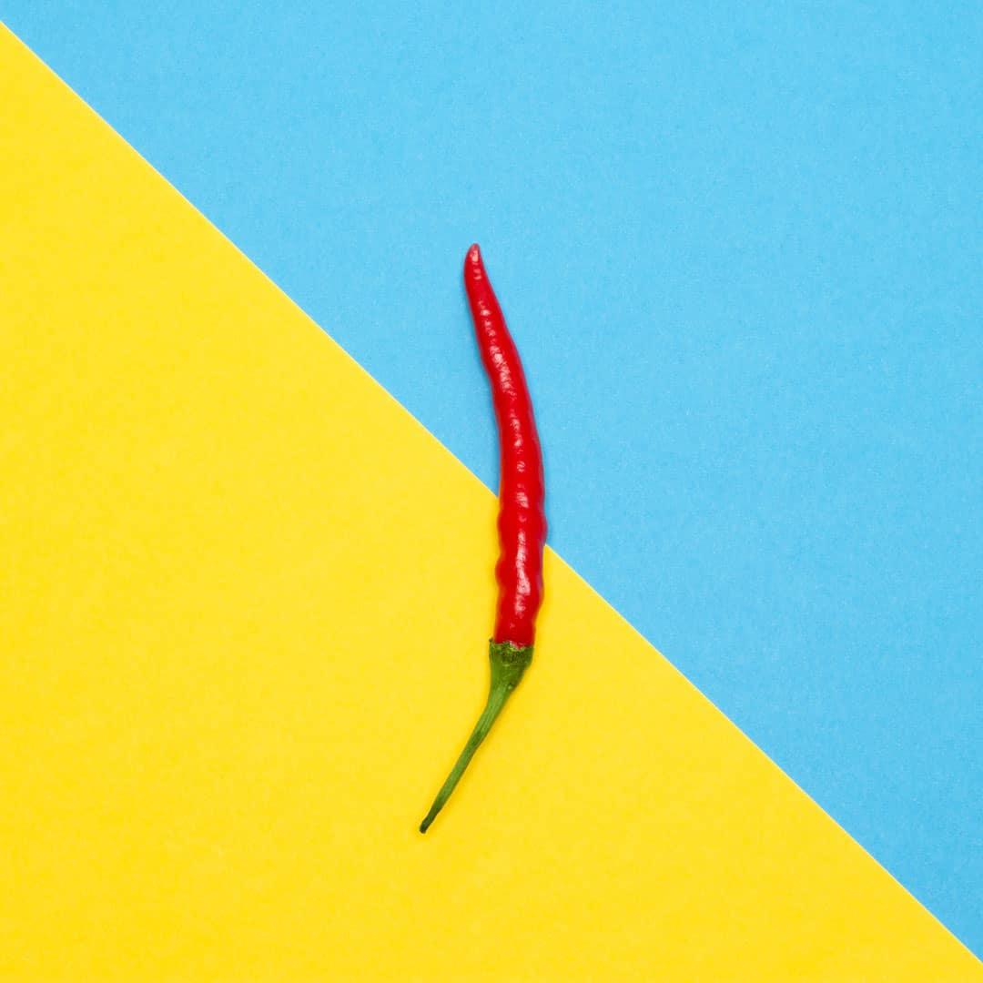 Peperoncino con sfondo due colori giallo e azzurro - Pimenta Group Web Agency Rimini
